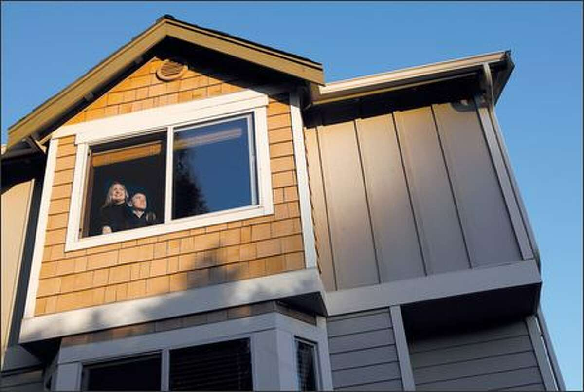 Holly Diehl and her son Frank Airey, 12, look at the view of Ballard from the master bedroom in her town house. Diehl, who is a single mother, has owned the home since August.