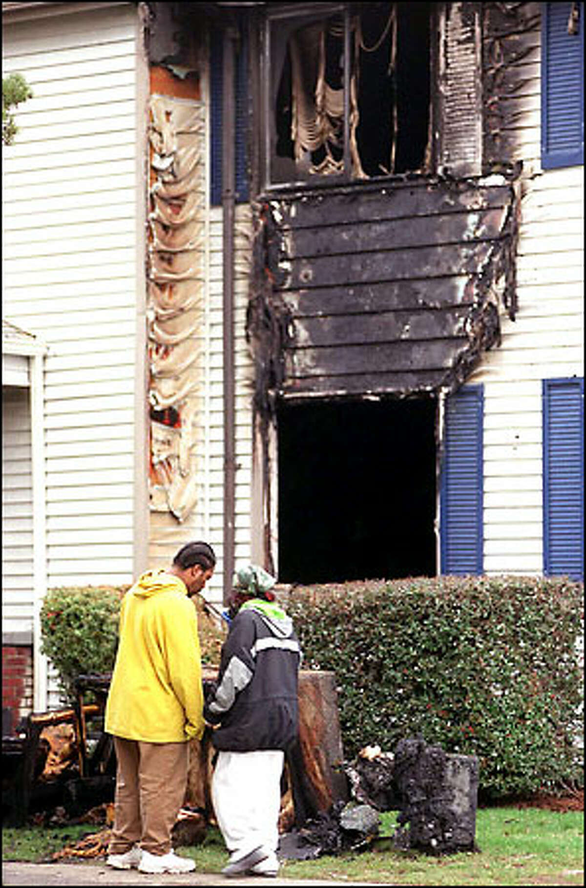 Residents of the Vintage Park apartments look over the aftermath of a fire in the Burien complex yesterday morning. More than 30 people were forced to evacuate, but housing was found for them. No injuries were reported.