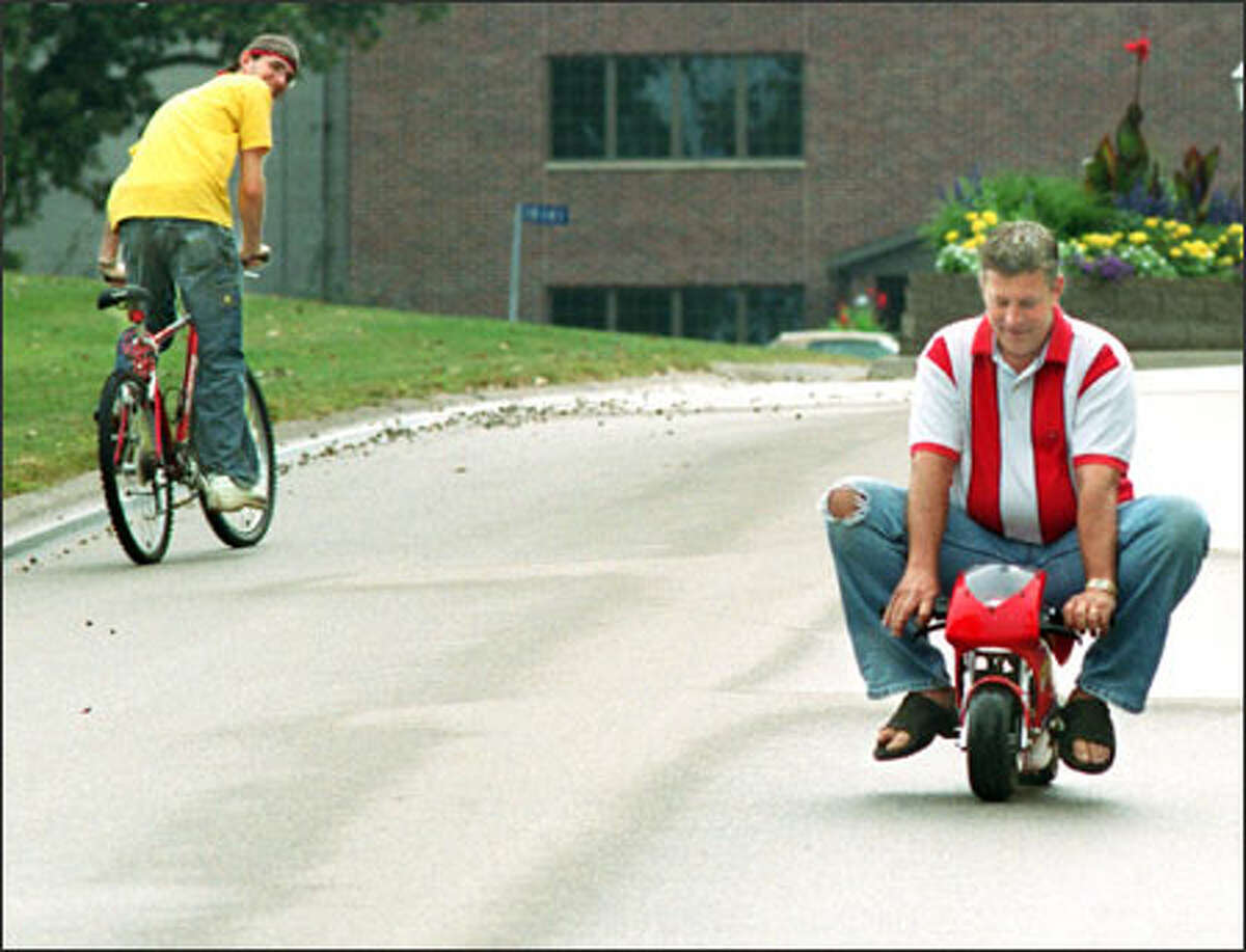 A bicyclist takes a second look at Tom Frick, riding a Blata minibike in Manchester, Iowa. The bike cost Frick $1,100, but some cost less than $200.