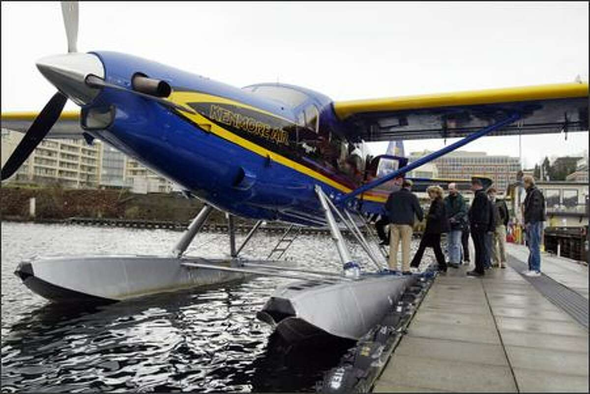 Passengers board a flight to Victoria, B.C., on Friday at Kenmore Air on Lake Union. Starting Dec. 31, sea and air travelers who enter the country from Canada must have a passport. Many businesses that rely on tourism, including Kenmore Air, are worried that people will skip trips rather than apply for the $97 document.