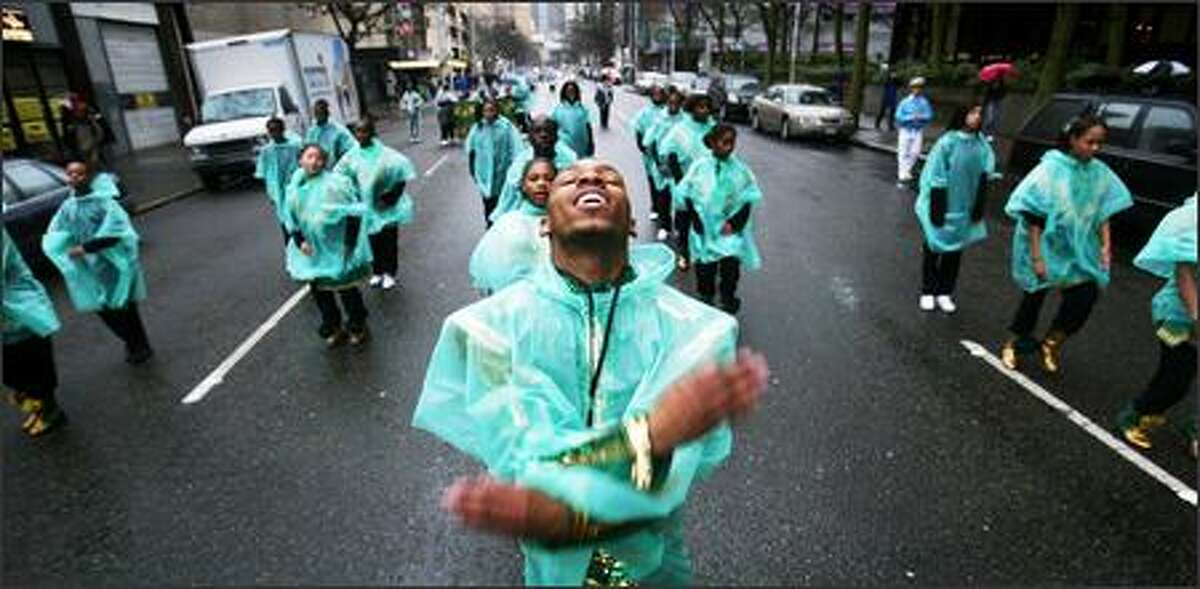 Dominic Hearvy, drum major of the Electronett Hi-Steppers Drill Team, leads his group Monday from Westlake Center downtown to the Seattle Center in the annual Martin Luther King Jr. parade. People celebrated the day and the civil rights leader's legacy for a variety of reasons.