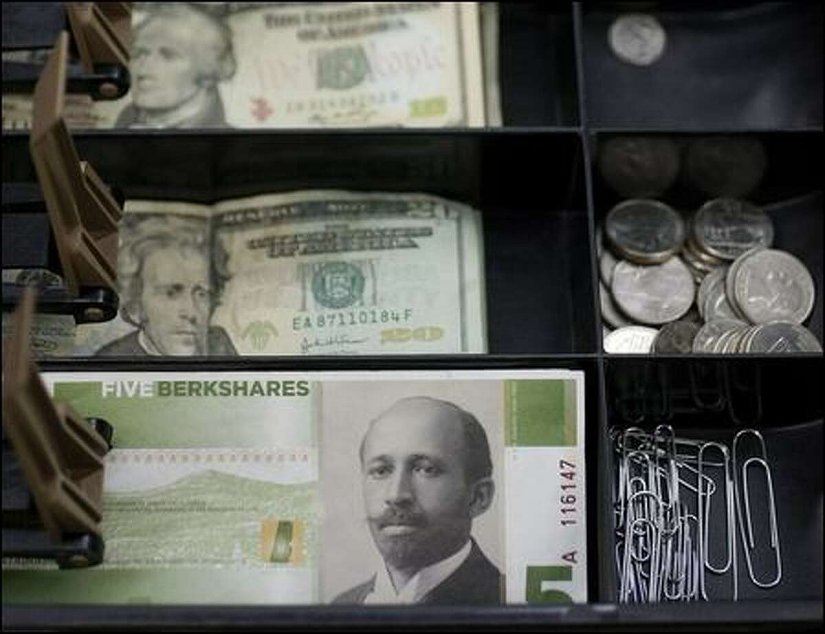 BerkShares featuring local artist Morgan Bulkeley Jr. sit alongside U.S. dollars in a cash drawer at the Berkshire Co-op Market.