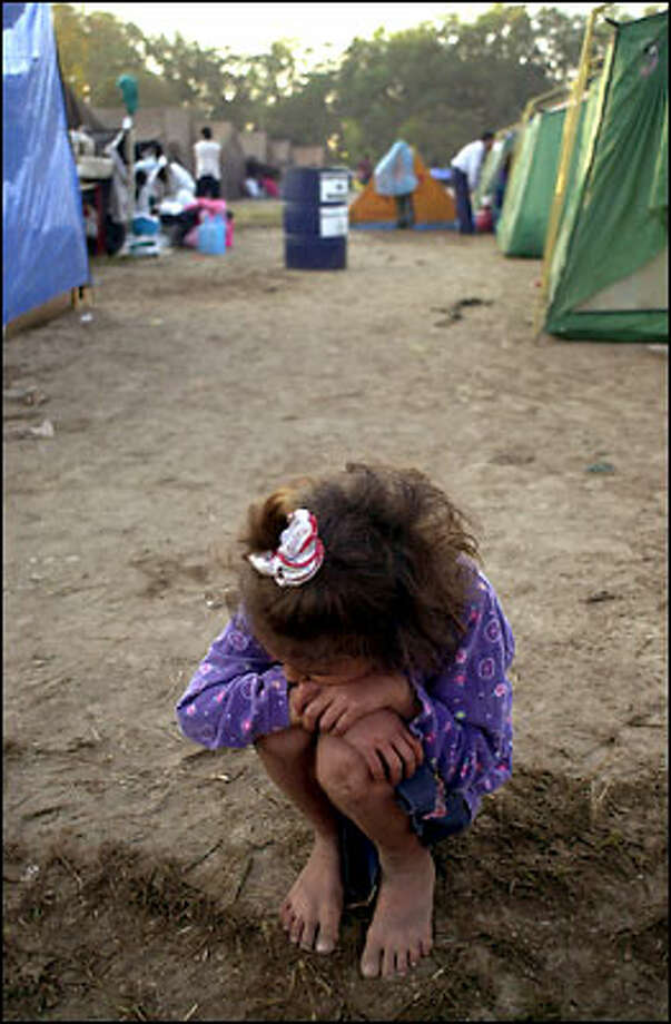 A child crouches in a camp for people made homeless by last Saturday's earthquake in El Salvador that killed nearly 700 people. Many of the survivors remain traumatized. Photo: Associated Press / Associated Press