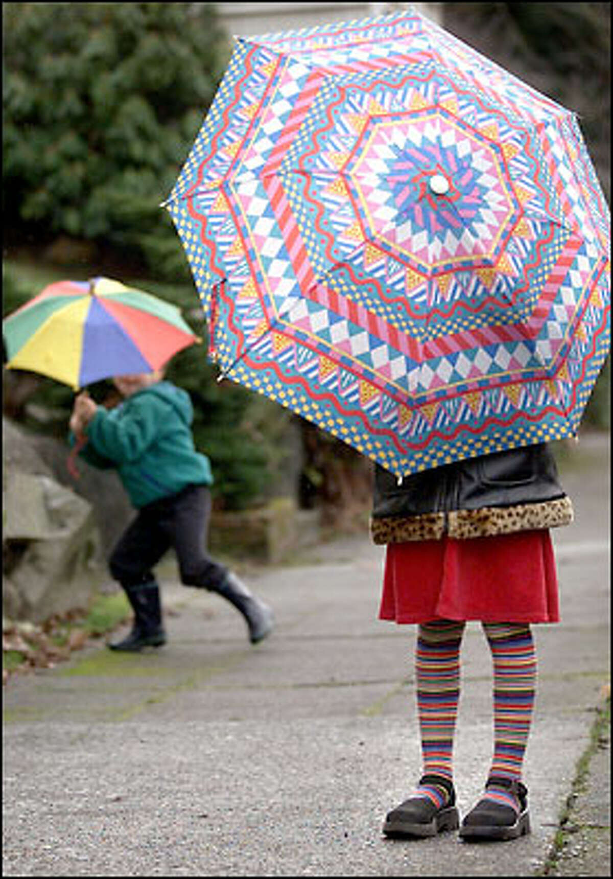 Madeleine Stein, 6½, and her brother Dylan, 4½, unfurl seldom-used umbrellas yesterday while walking home during a sprinkle from John Hay Elementary School on Queen Anne. Seattle can expect a chance of rain this morning and increasing rain tonight and tomorrow.