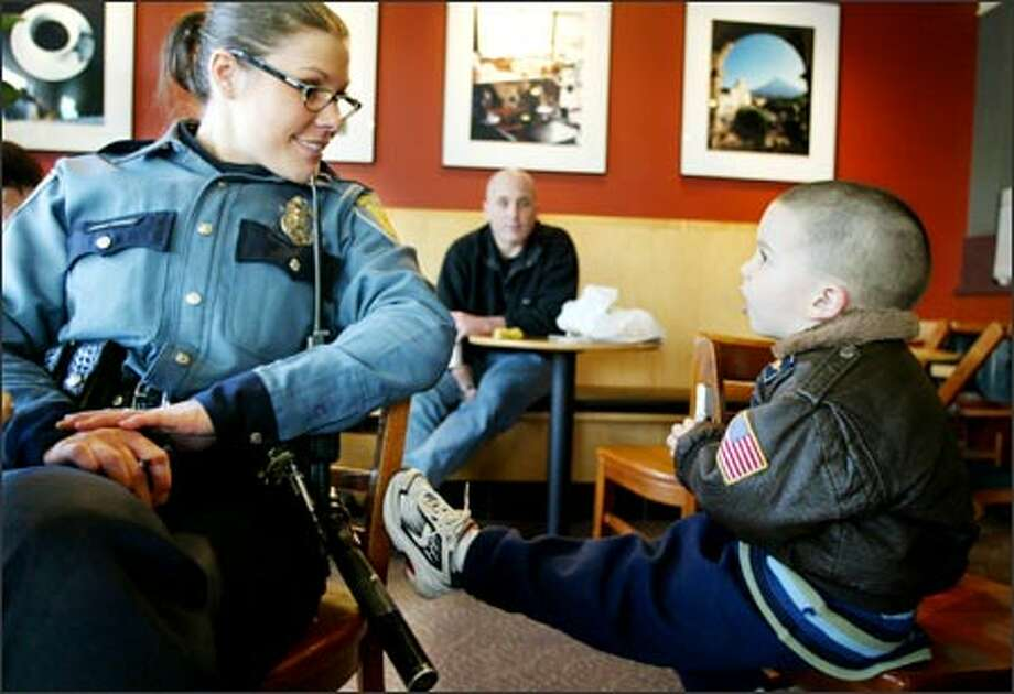 Officer Daina Boggs talks to Jack Durham, 4, at a Starbucks in West Seattle as dad, Matt Durham, watches. Boggs will move to the Southwest Precinct when it opens. Photo: Meryl Schenker, Seattle Post-Intelligencer / Seattle Post-Intelligencer