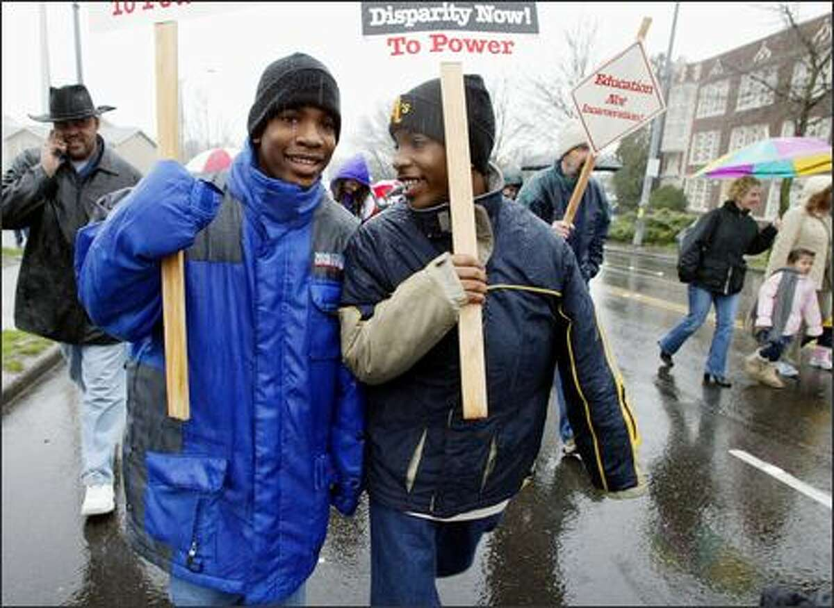 Thirteen-year-old twins Leon, left, and William Gray of Seattle march in the MLK Day march to the federal courthouse in downtown Seattle after the rally in the Garfield High School gym.