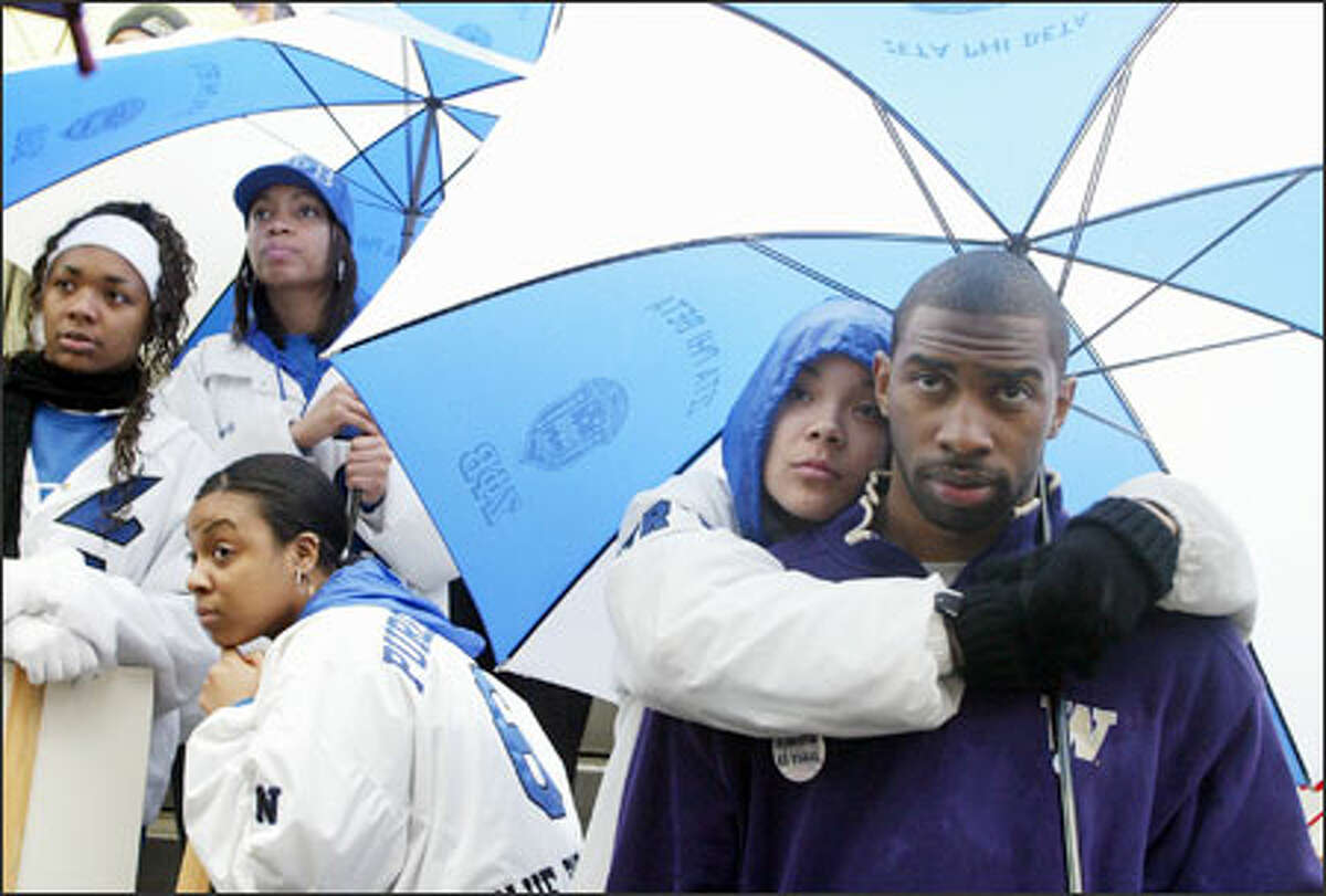 Lacie West and Shelton Sampson listen to Martin Luther King Jr. Day speakers in downtown Seattle after a rally at Garfield High and march to the courthouse. At left are West's Zeta Phi Beta sorority sisters; left to right, Essence Batson, April Bowman (in cap) and Caroline Jordan.