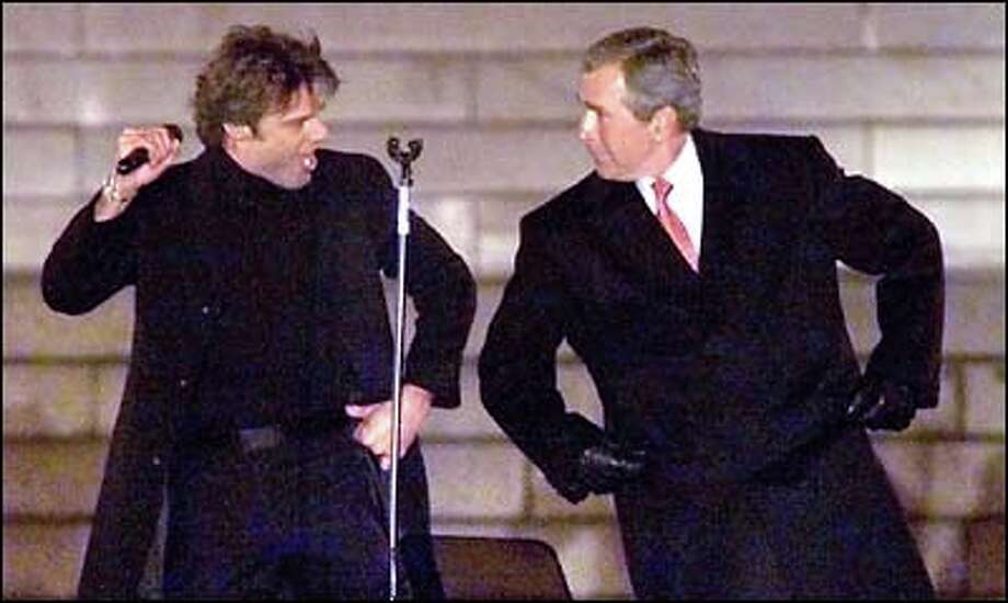 President-elect George W. Bush and singer Ricky Martin share the stage and a few moves in the Inaugural Opening Celebration yesterday at the Lincoln Memorial. While some discussed Bush's environmental stands, most in Washington, D.C., were preparing for weekend inaugural activities. Photo: Associated Press / Associated Press