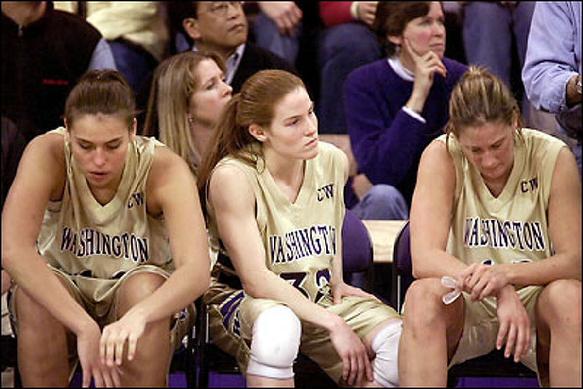 Washington players, from left, Andrea Lalum, Jill Pimley and LeAnn Sheets, sit dejectedly as time runs out in their loss to Oregon in Bank of America Arena.
