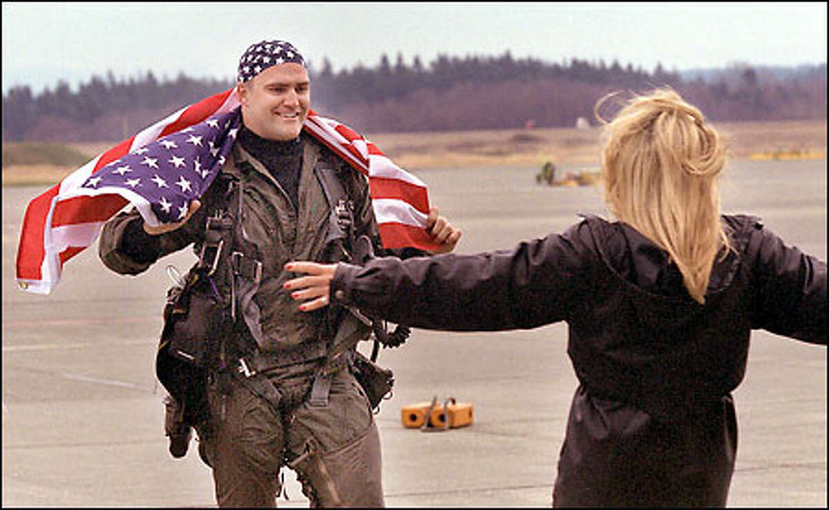 Navy pilot Lt. Mathew Kaslik greets his girlfriend on his return to Whidbey Island yesterday after six months at sea aboard the aircraft carrier USS Carl Vinson.