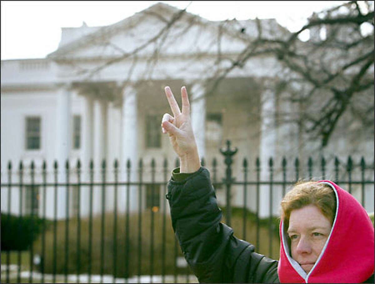 Anti-war protester Barbara McGovern, of Westfield, Mass., flashes a peace sign in front of the White House today. Thousands of people marched through the streets of Washington, D.C., this weekend to protest military action in Iraq.