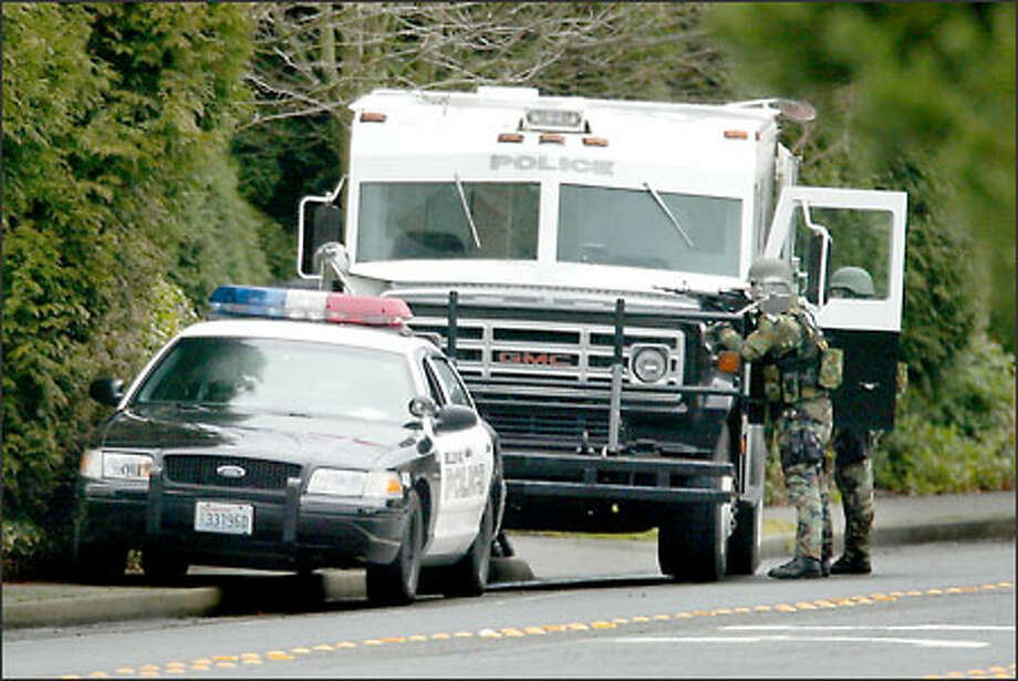 Bellevue SWAT team members focus on the Embassy Suites Hotel, where more than 200 guests were trapped for 4 1/2 hours yesterday morning as FBI agents negotiated with three men wanted in a Missouri bank robbery. Photo: Gilbert W. Arias, Seattle Post-Intelligencer / Seattle Post-Intelligencer