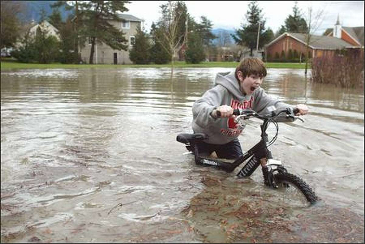 Chris Conley, 12, pushes his bike through a flooded portion of River View Park next to the Snoqualmie River in Snoqualmie yesterday. The river was expected to reach major flood levels near Carnation, and flood warnings were issued for several other rivers. The rain brought with it a record high of 60 degrees at Sea-Tac Airport.
