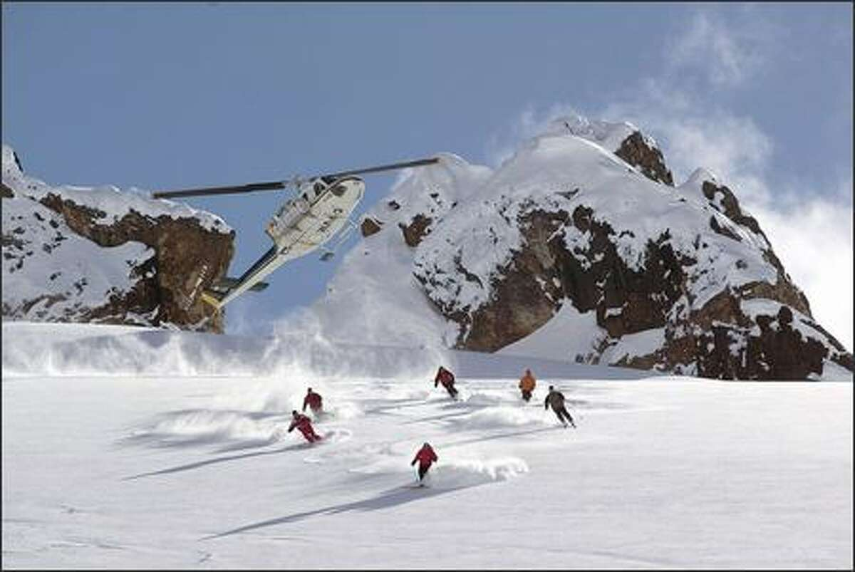 A Bell 212 helicopter leaves a group on a glacier in the Monashee Range. Skiers who prefer snowcat options can choose from two outfitters in the Monashees: Mustang Powder on the Mustang glacier and Monashee Powder Snowcats, just east of Silver Star Mountain Resort.