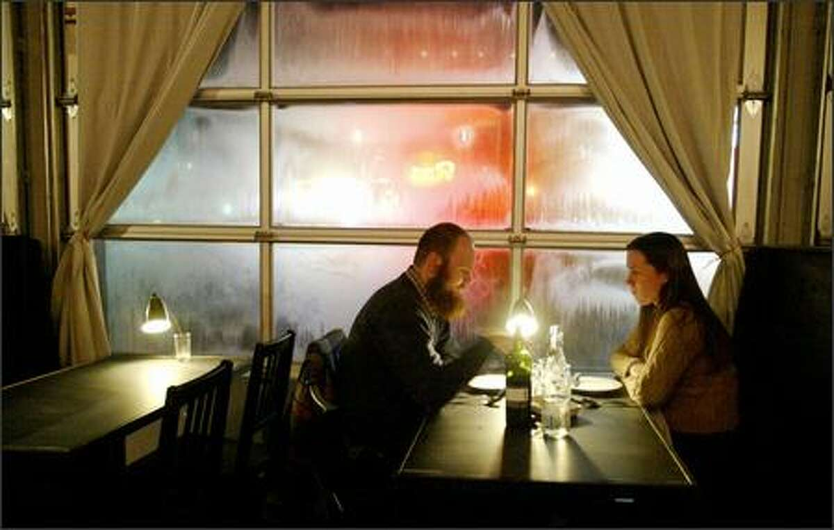 Gavin Tierney and Susan Knightly sit next to steamy glass doors at The Station Bistro, a renovated Ballard service station where most dishes are a bargain at $9 a pop. The food falls into a category somewhere between pub grub and epicurean.