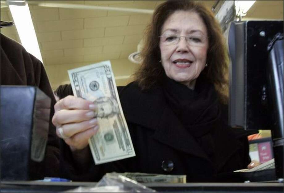 "Stephanie Collins counts out cash as she pays for groceries at a PCC Natural Market grocery store Friday in Seattle. President Bush, acknowledging the risk of recession, embraced about $145 billion worth of tax relief Friday to give the economy a ""shot in the arm."" (AP Photo/Elaine Thompson) Photo: Associated Press / Associated Press"