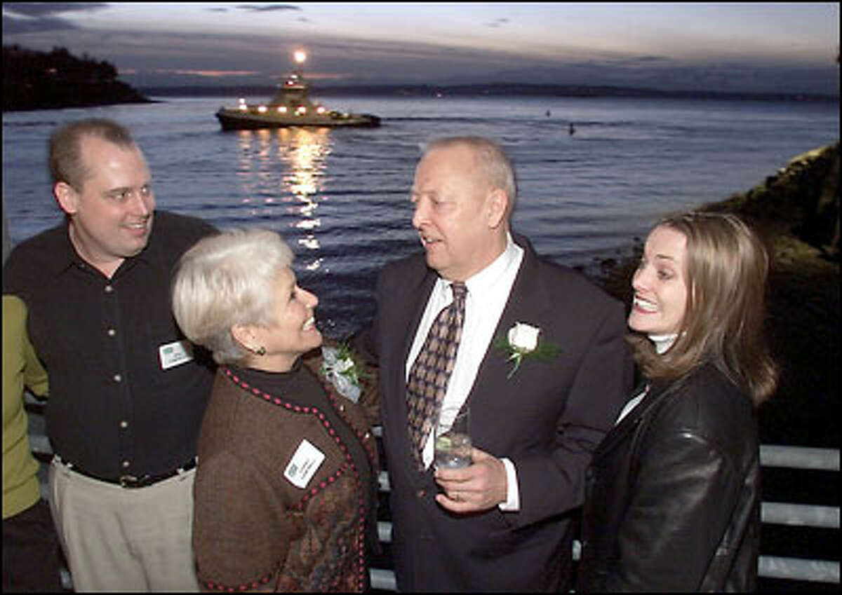 As a Foss tug toots a salute, Pete Campbell enjoys his retirement party Friday evening.