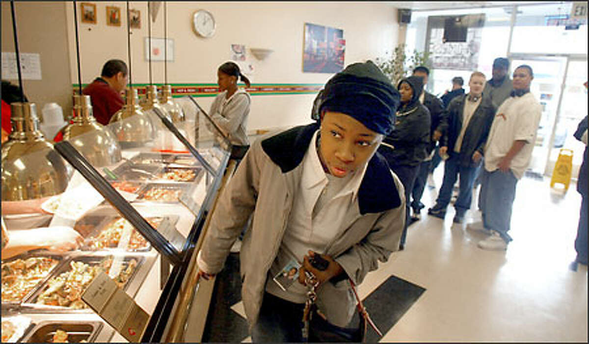 De'Andra Charlston, a junior at Garfield High School, checks out the fare at the Magic Dragon, a Chinese fast-food eatery at the corner of 23rd and Jackson in the Central Area.