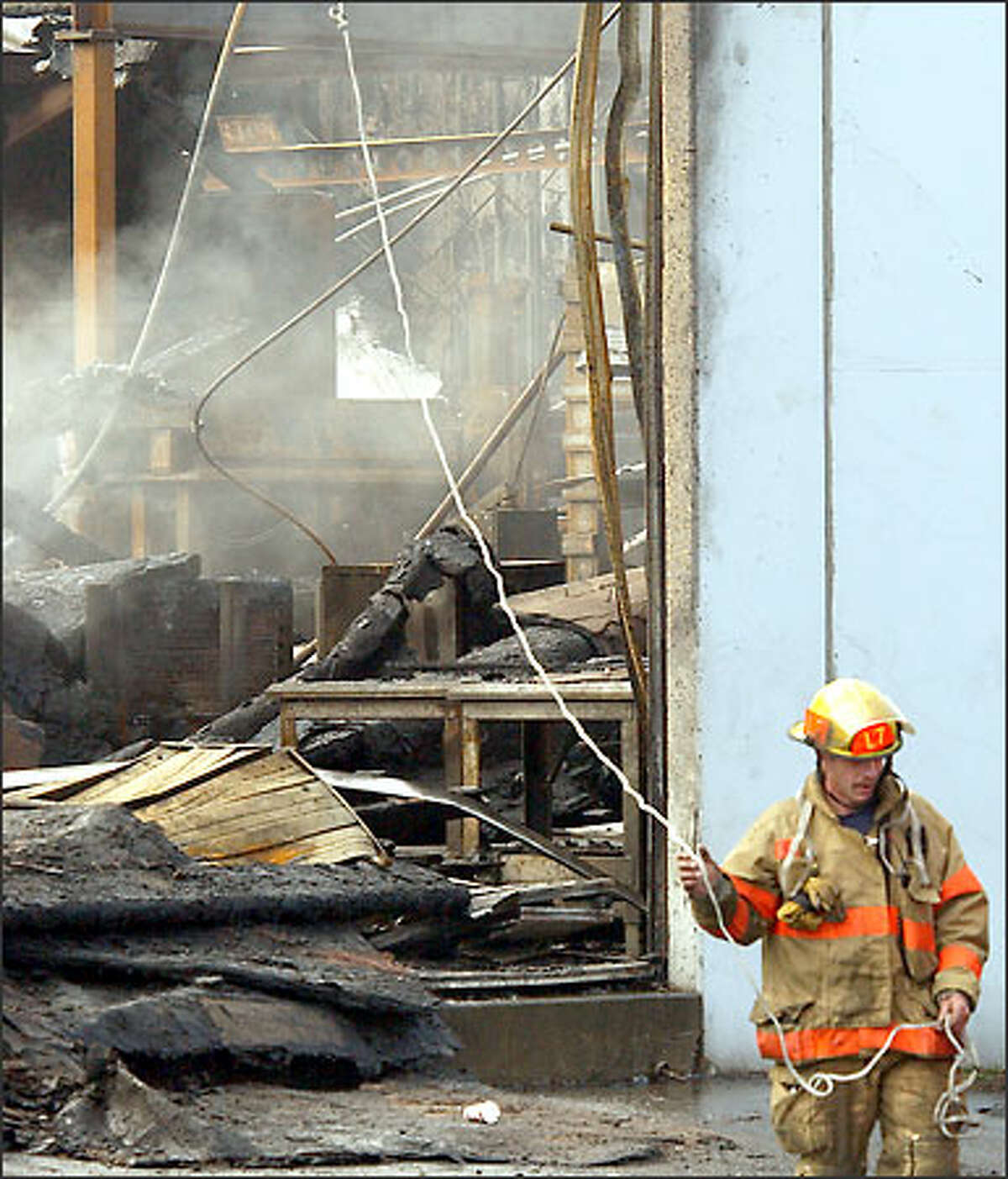 A Seattle firefighter drags a line that guides an overhead nozzle in an effort to put out a still-smoldering fire at Capital Industries, a Georgetown metal-fabricating company. The main building of the third-generation family business was destroyed by the blaze Sunday.