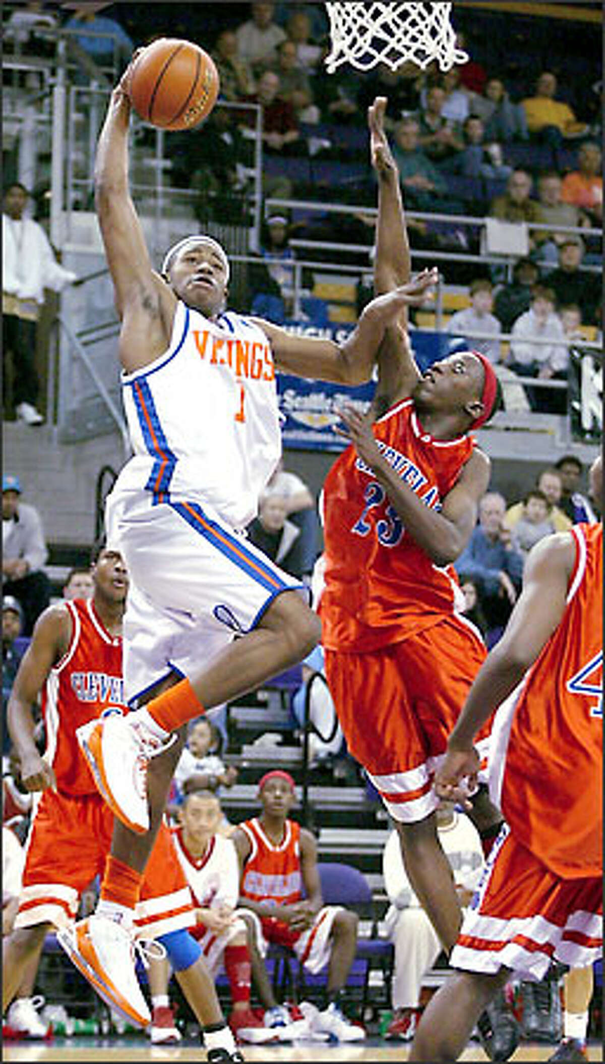 Terrence Williams of Rainier Beach fends off Cleveland defender Jason Pegues on a drive to the basket during the marquee game of the King Holiday Hoopfest yesterday at Hec Edmundson Pavilion. Williams scored a game-high 23 points and Rainier Beach withstood a fourth-quarter Cleveland rally for a 70-66 victory.
