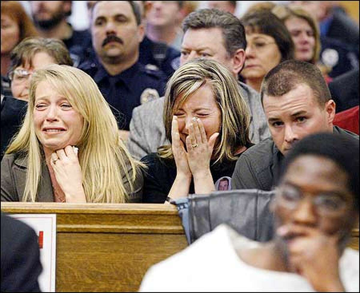 Sisters of Des Moines Police Officer Steven Underwood, Lynnea Stanley, left, and Angela Daninger, along with Ron Daninger, listen and react as 911 tapes are played at the sentencing hearing of Charles Champion, bottom right foreground, in the officer's March 7, 2001. During the hearing, Champion apologized to the family for the first time, saying he is ashamed and sorrowful for what happened. He was sentenced to the maximum 34 years.