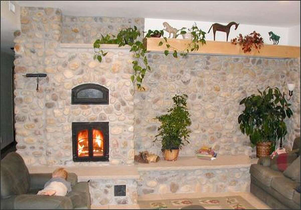 There's an opening for a baking oven in this large fireplace finished with stone along the wall. (GIMME SHELTER)