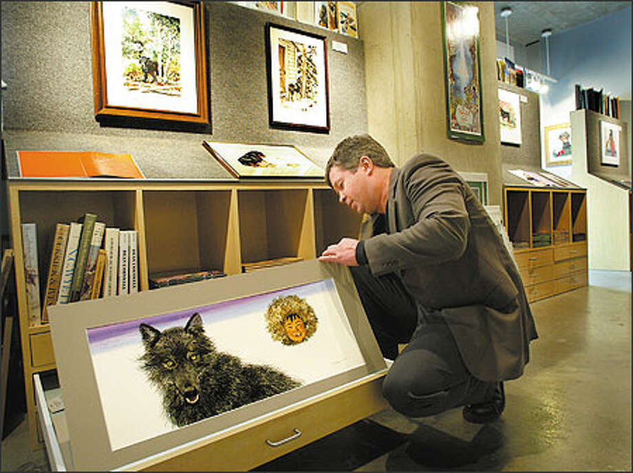 "Owner Scott McCallum looks through some of the drawers of original children's book artwork in his First Avenue gallery, Art of Illustration. The work includes Ted Rand illustrations from the book, ""Nutik, the Wolf Pup."" Photo: Scott Eklund, Seattle Post-Intelligencer / Seattle Post-Intelligencer"