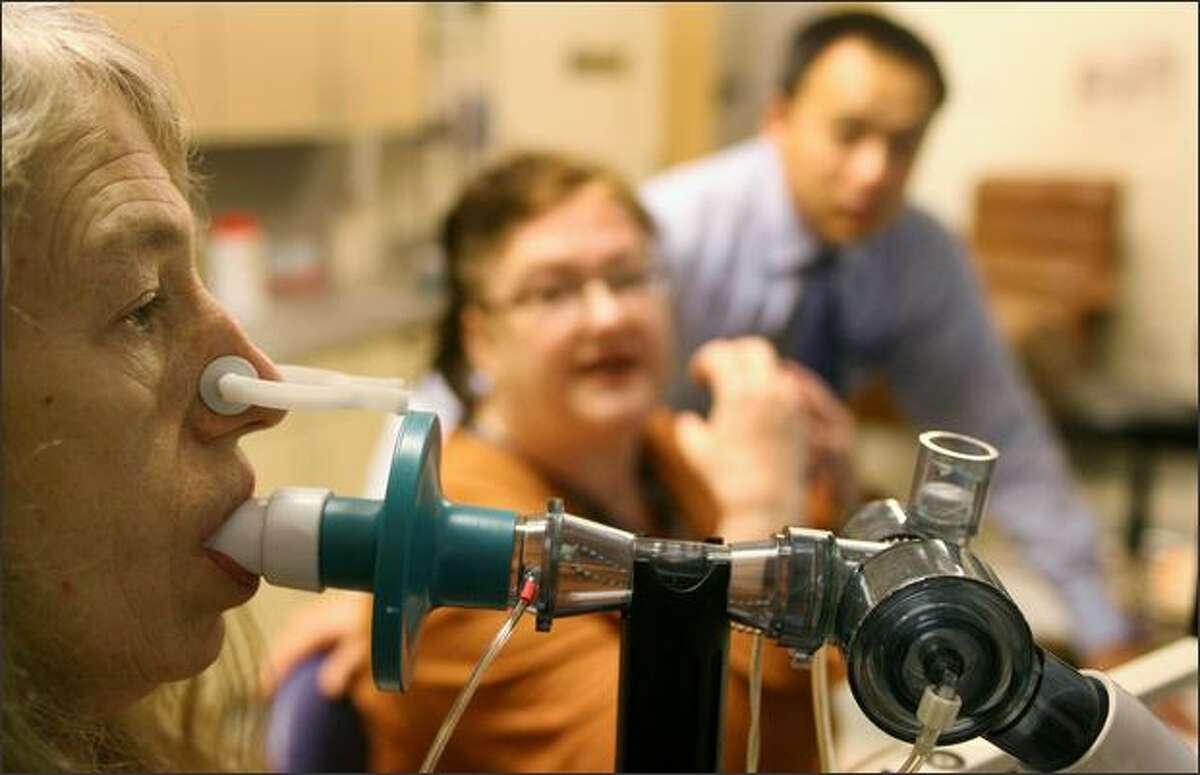 Janet Cothrell and Dr. Jason Chien, background, observe a patient as she breathes into a spirometer to measure her lung capacity Friday at the Seattle Cancer Care Alliance.