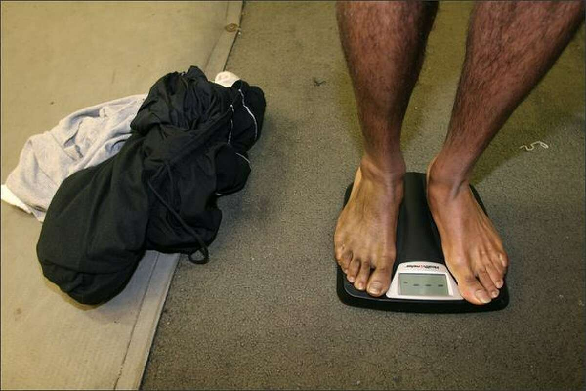 After dropping all his clothes, boxer Eddie Hunter weighs in on an electronic scale to see if he made his weight class during training at Bumblebee Boxing Club.