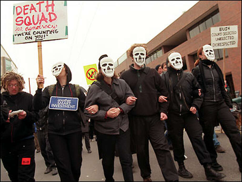 "Proclaiming the ""death of democracy"" because of the inauguration of President Bush, demonstrators march past Seattle Central Community College along Broadway on Capitol Hill. Rallies on campus often draw participants from the neighborhood. Photo: Jeff Larsen, Seattle Post-Intelligencer / Seattle Post-Intelligencer"