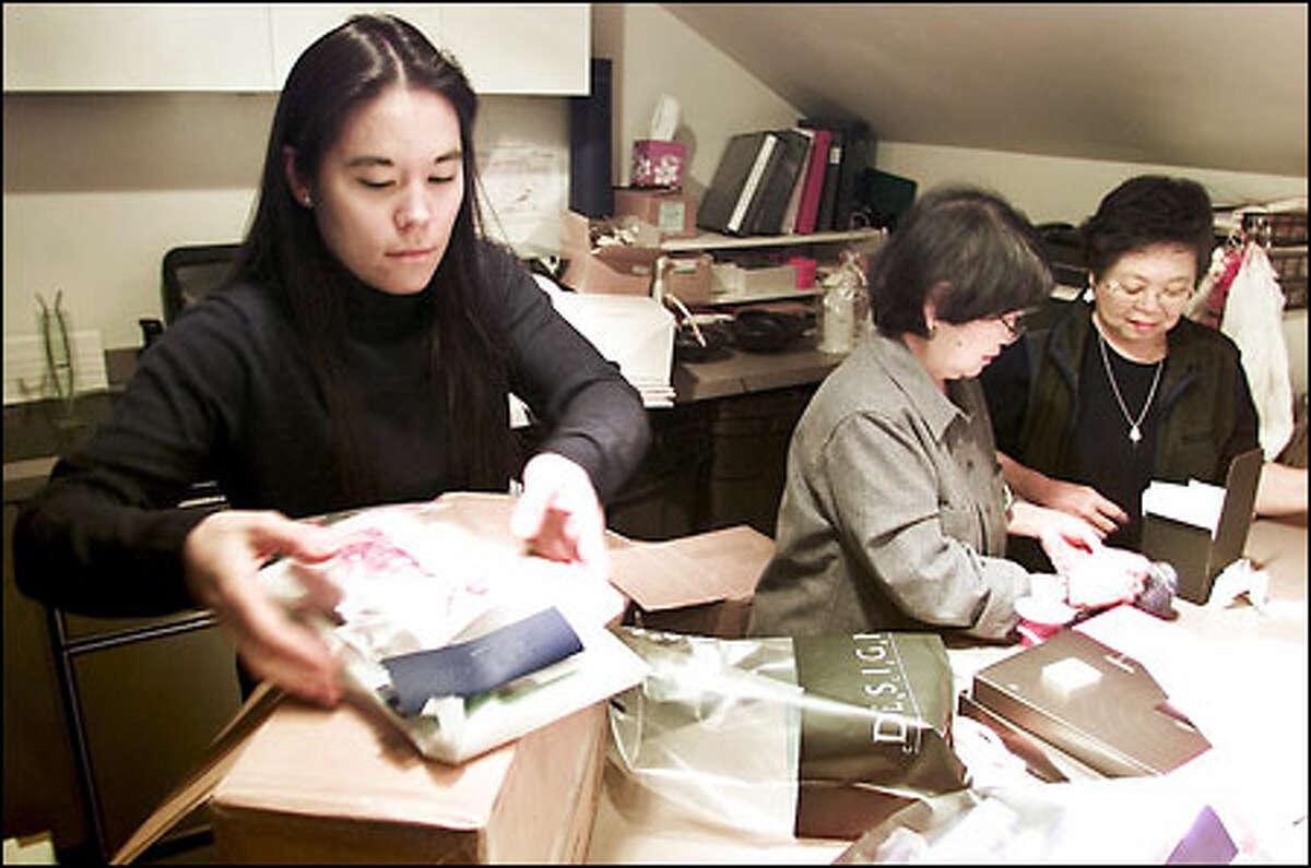 Kris Kadoshima, owner of Design Concern, packs gift bags with mother Arlene Kadoshima, center, and aunt JoAnn Sugasawara, at City Center Mall.