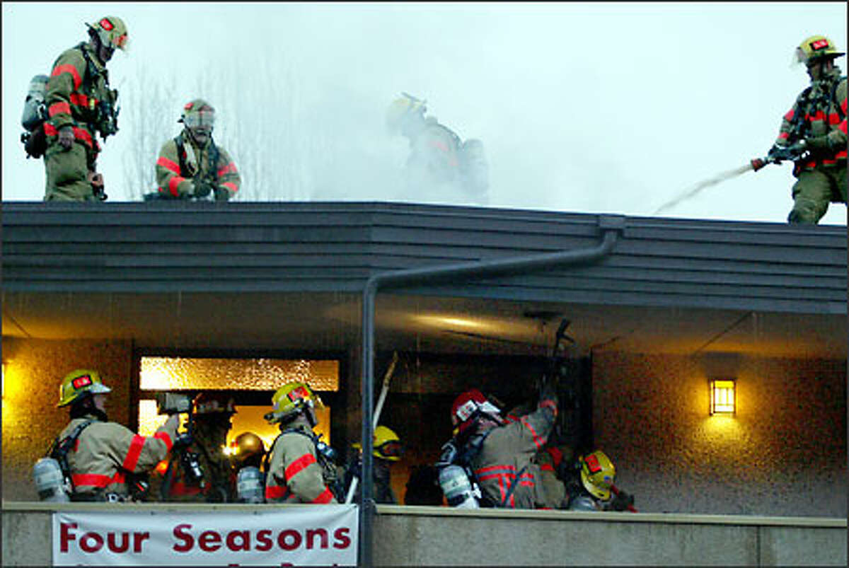 Seattle firefighters work from above and below to put out a stubborn roof blaze at Four Seasons Apartments on Boyer Avenue East in the Portage Bay neighborhood. No injuries were reported in the fire, which was started by hot tar from roofing repair work. Damage was estimated at $55,000.