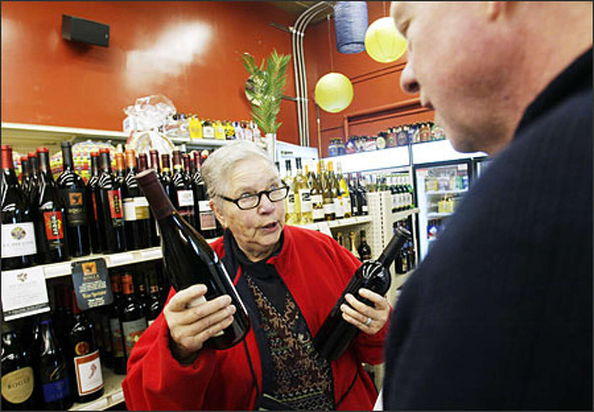 Delphine Bowers, left, who lives in Phinney Ridge, chats with Wally Wright, co-owner of the new Phinney Market, about the wine club offered at the store.