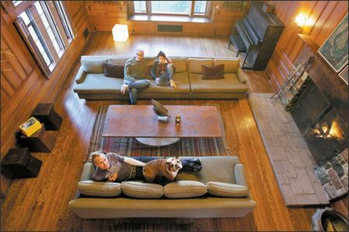 Wade Weigel, top, with son Jason and Jeff Ofelt, relax in the great room of their historic, 1933 home in the northwest Seattle neighborhood of North Beach. They were initially intimidated, but bought it last month.