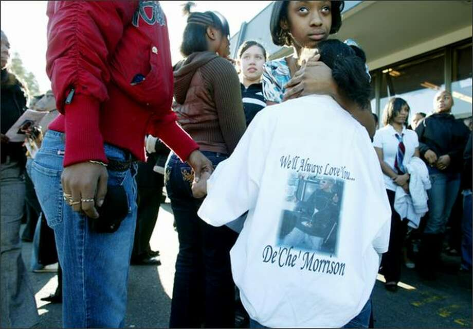 Jamazia Brown, 8, in a shirt in honor of her 14-year-old cousin De'Ché Morrison, holds the hand of her stepmother, Jimmia Brown, at Morrison's funeral Tuesday. Photo: Paul Joseph Brown, Seattle Post-Intelligencer / seattlepi.com
