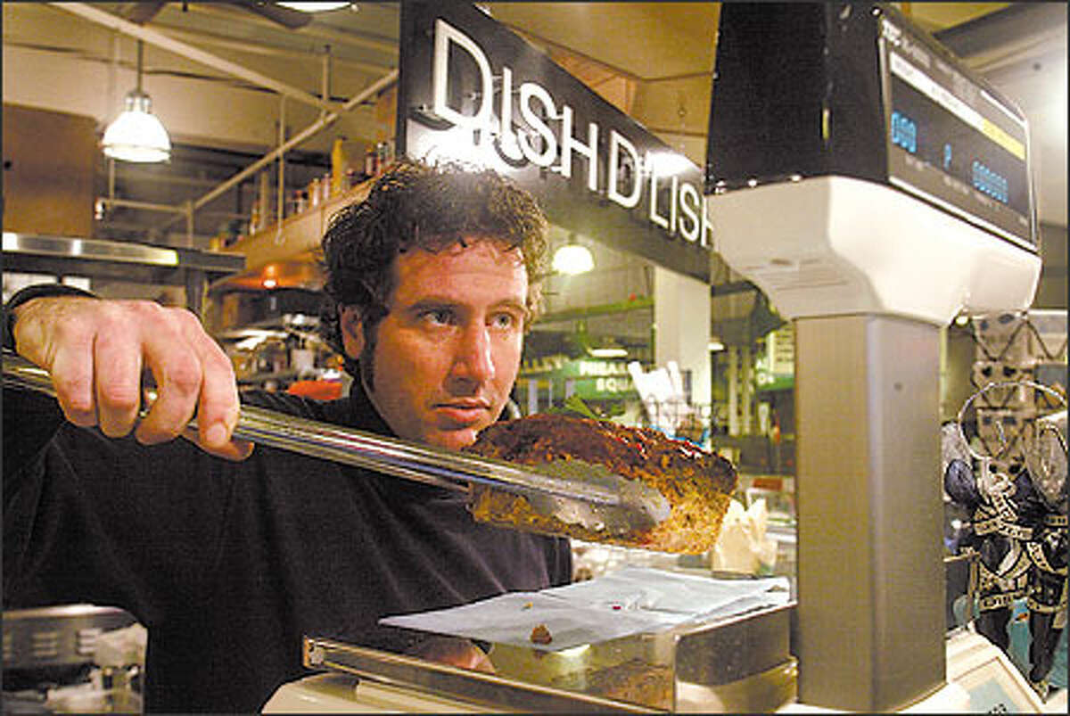 """Counterman Daveed Yeast weighs a hunk of meat loaf for a customer at Kathy Casey's Dish D'Lish, which bills itself as """"food t' go-go,"""" in the Pike Place Market."""