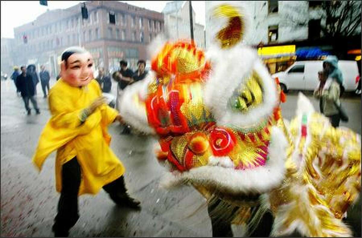 As part of lunar new year, members of Mak Fai Washington Kung Fu Club perform a lion dance outside a business on South Jackson Street in Seattle's International District yesterday. Tradition has it that the dance will drive away evil spirits and bring the business good fortune. A festival celebrating the Year of the Monkey will be from noon to 6 p.m. today at Union Station.