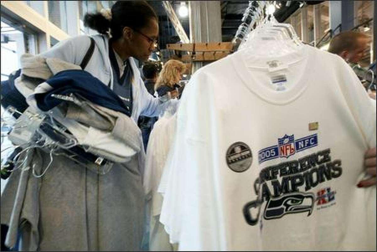 Holding an armful of merchandise, Darlene Adams of Seattle looks through a rack of NFC Champions T-shirts at the Seahawks Pro Shop at Qwest Field.