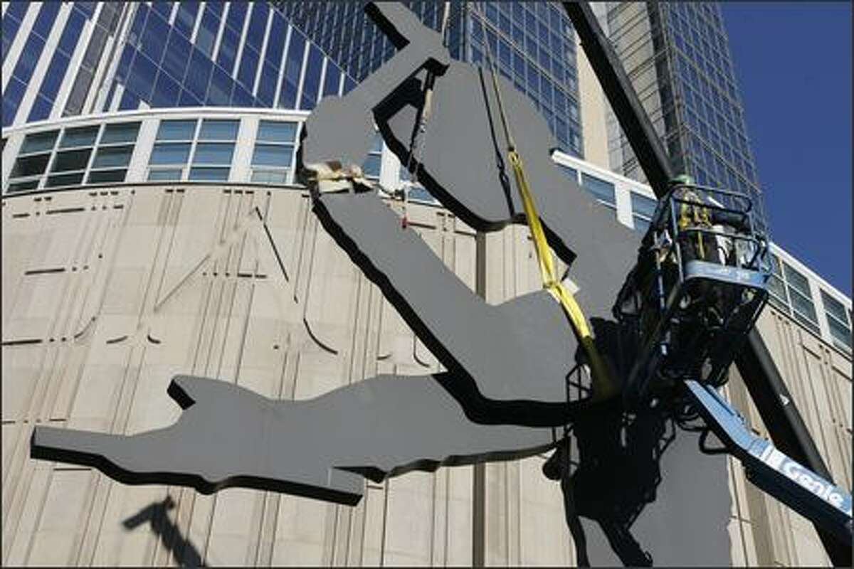 Workers with Fabrication Specialties of Seattle use a lift as they prepare to remove the broken arm of the Hammering Man sculpture on Wednesday in downtown Seattle. The 48-foot tall Seattle icon has had its arm in a sling after the mechanism that moves the arm broke in March of 2006. The sculpture located in front of the Seattle Art Museum since September 1992, was commissioned by the Seattle Art Commission and was created by artist Jonathan Borofsky.