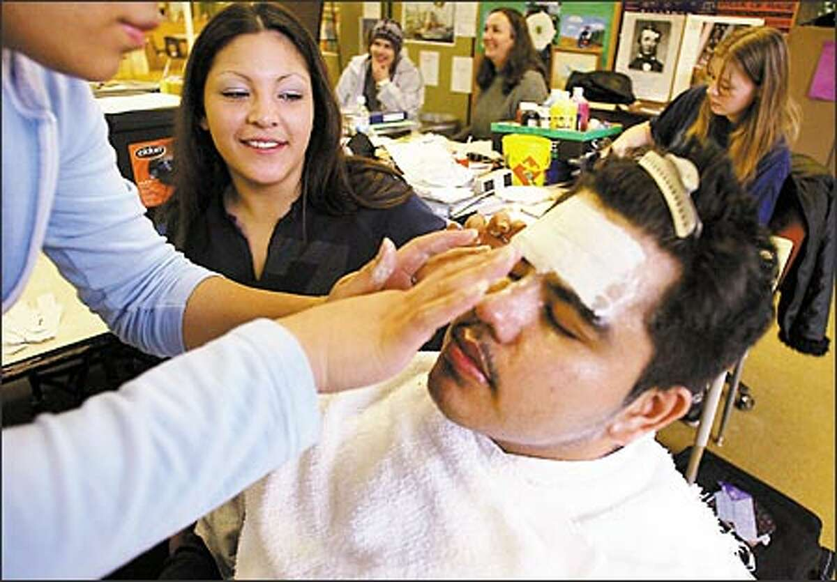 A hands-on assignment: Truman Center student Priscilla Basher helps apply a mask to Jose Flores. Their task is to create masks to reflect their feelings.