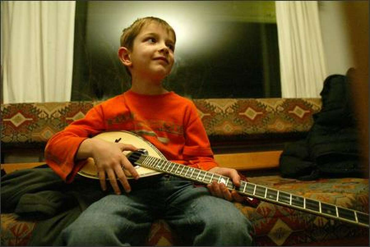 Bobby Govetas, 7, strums a bouzouki while he watches his parents, Ruth Hunter and Christos Govetas, rehearse.