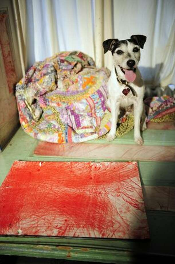 Doggie artist Tillamook Cheddar, or Tillie, a Jack Russell terrier, looks on as owner Bowman Hastie signs copies of her biography in New York in this August 2009 file photo. The 10-year-old dog has been painting since she was a puppy and collaborated with major established artists like Tom Sachs and Jon Kessler. Tillie's owner, Bowman Hastie, who describes himself as her assistant, has been promoting her paintings, which sell for more than $1,000 via art shows and galleries. Photo: Getty Images / Getty Images