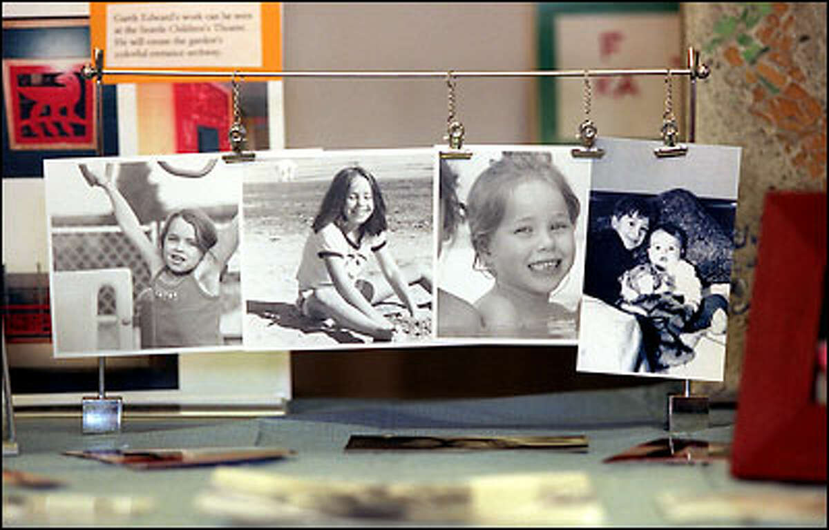 Photographs of the four John Hay Elementary students who were killed on board Flight 261 one year ago are mounted on a table at the school. From left: Blake and Coriander Barnett-Clemetson, Rachel Pearson and Miles J. Clemetson, shown with his 6-month-old brother, Spencer, who also died in the crash.
