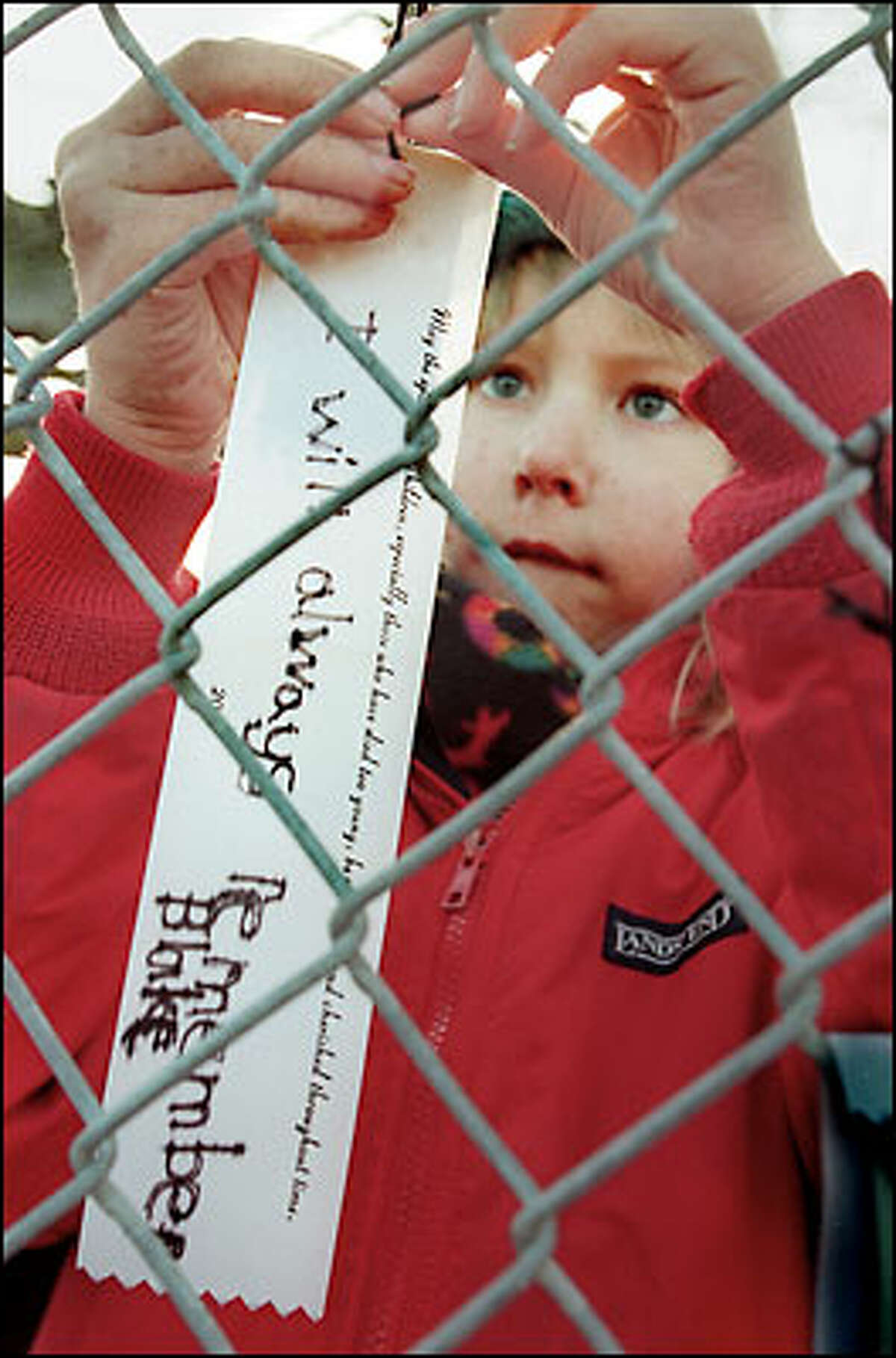 John Hay Elementary first-grader Corby Johnson ties a ribbon to a fence with a message to friend Blake Barnett-Clemetson, who died in the crash of Alaska Airlines Flight 261 in January 2000. The school broke ground on a memorial garden for crash victims yesterday.