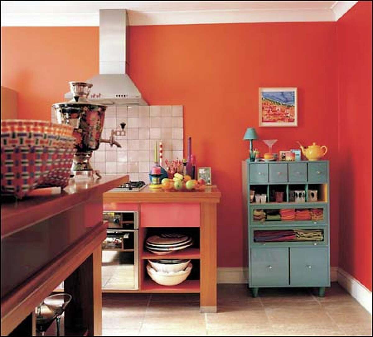 Using a bold color such as red gives balance to a kitchen dominated by bright lights, neutral tiles and a white ceiling.