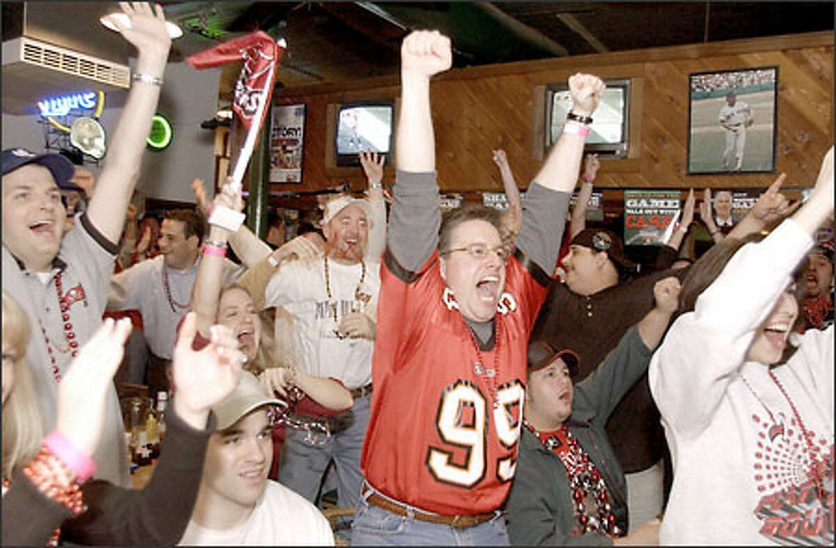 Tampa Bay Buccaneers fans celebrate as they watch their team score against the Oakland Raiders in the third quarter of Super Bowl XXXVII, at Beef O' Brady's sports pub in Tampa, Fla.