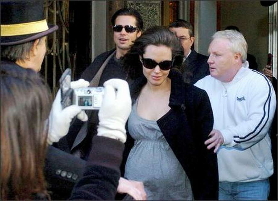 No question any longer that Angelina's tummy is in the expand-o mode, judging by this photo from London. Ms. Jolie & Mr. Pitt exit their hotel and head to the airport to join the throngs of power brokers and activist celebs gathered in Davos, Switzerland, for that annual romp known as the World Economic Forum. Photo: Associated Press / Associated Press