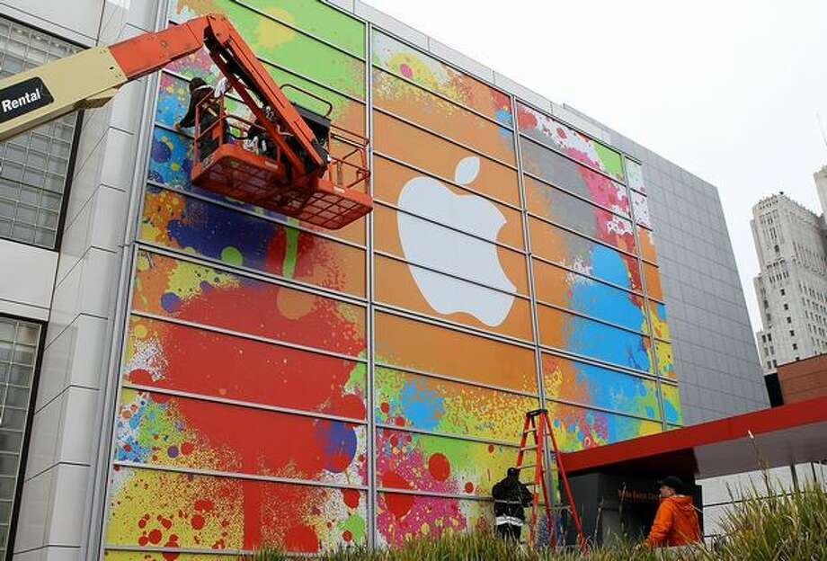 Workers apply the Apple logo to the exterior of the Yerba Buena Center for the Arts in preparation for an Apple special event Wednesday in San Francisco, where CEO Steve Jobs is expected to unveil a new Apple tablet computer. Photo: Getty Images / Getty Images