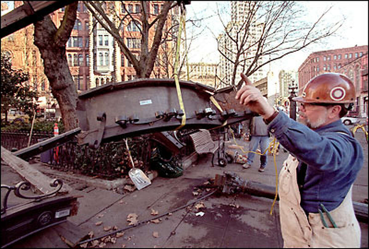 Gary Johnson of Anthony Construction directs as one piece of the Pioneer Square pergola is lifted away. The pergola, destroyed Jan. 15 when a truck ran into it, will be rebuilt at another location and returned to Yesler Way and First Avenue