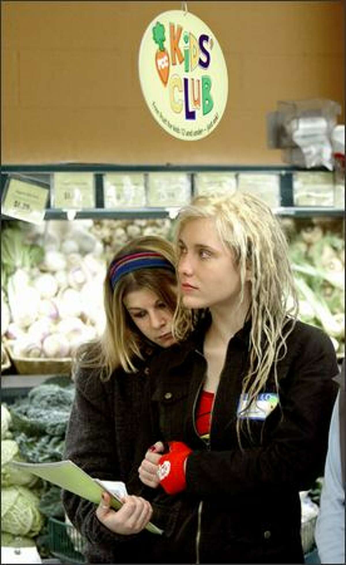 Sydney Smith, 15, left, and Naomi Picinich, 17, listen to a talk about organic foods at the Seward Park PCC.